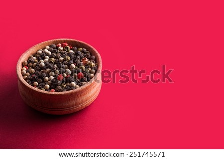 assorted peppers in a wooden bowl on vinous background