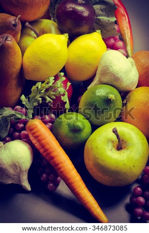 Assorted pile of different colorful fake fruits and vegetables
