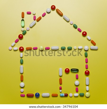 Assorted pills creating house shape - stock photo