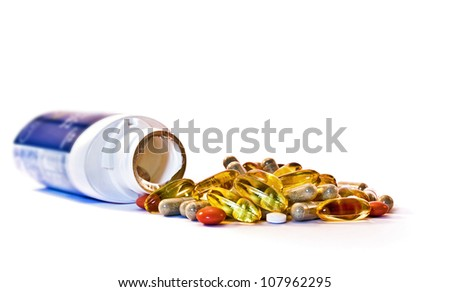 Assorted pills displayed with opened bottle and a mixture of types - stock photo