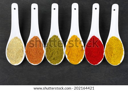 Assorted powder spices in white spoons on black wood. Top view point. - stock photo
