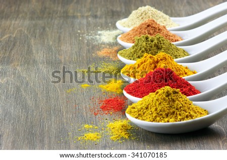 Assorted powder spices in white spoons on wood.