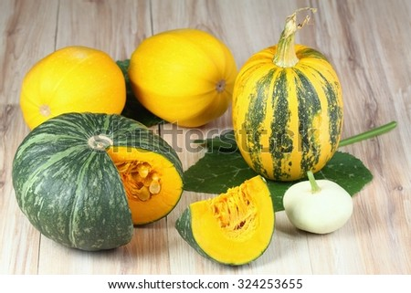 Assorted pumpkins and squashes on rustic wooden board - stock photo