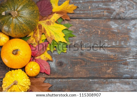 Assorted pumpkins with autumn leaves on wooden table