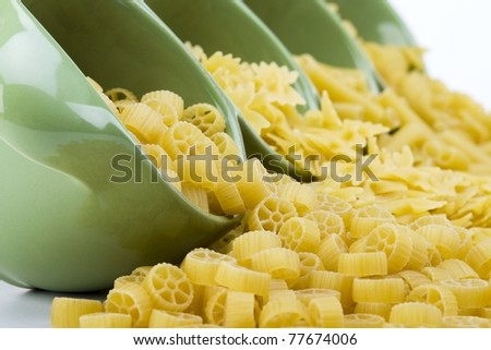 Assorted raw pasta noodles spilling from a green ceramic dish closeup