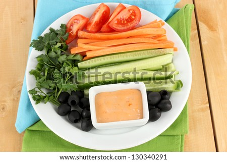 Assorted raw vegetables sticks in plate on wooden table close up