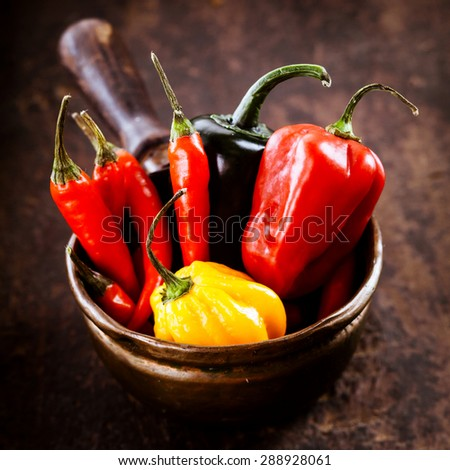 Assorted Red hot cayenne chili peppers,habanero colorful yellow and red sweet pepper displayed ready for cooking in a rustic bowl on a wooden counter - stock photo
