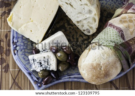Assorted rustic bread with assorted olives and cheeses from a top down view - stock photo