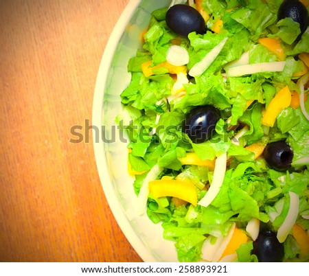 Assorted salad of green leaf lettuce with squid and black olives, close up. Instagram image retro style - stock photo