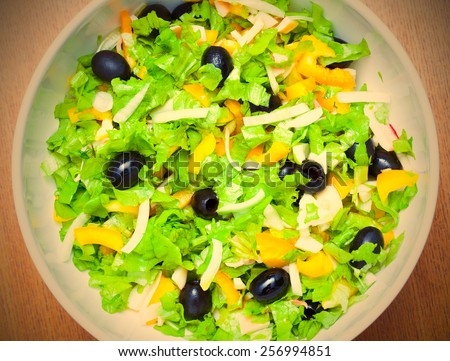 Assorted salad of green leaf lettuce with squid and black olives. instagram image retro style - stock photo