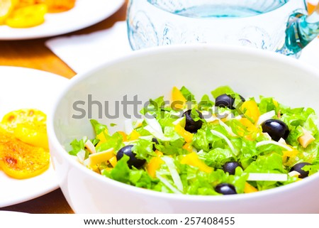 Assorted salad of green leaf lettuce with squid and black olives on lunch table, close up - stock photo