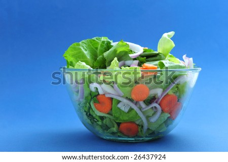 Assorted salad on bowl, on blue background
