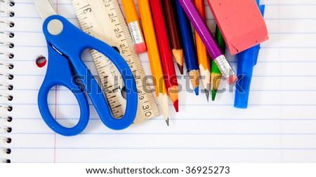 Assorted school supplies with a notebooks, pencils, pens, scissors etc. - stock photo