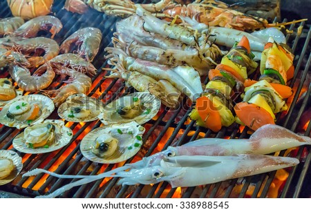Assorted seafood on the grill with flames closeup of delicious grilled sea food - stock photo
