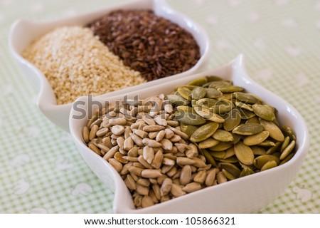 Assorted seeds in bowl pumpkin, sunflower, sesame, flax - stock photo