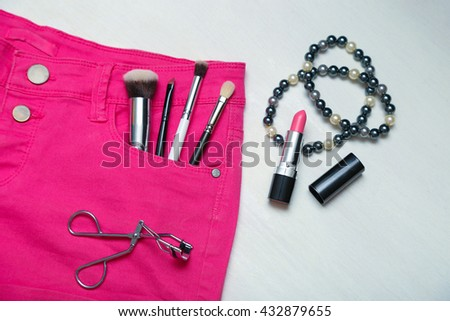 Assorted set of make up brushes and tools on pink jeans shorts, on white wooden background. Pearl black and white necklace - stock photo