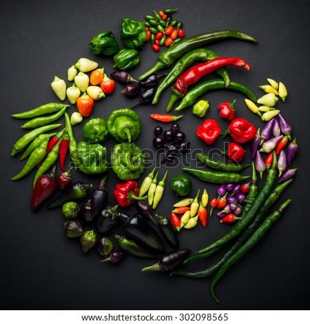 Assorted sharp hot pepper on a black background, overhead view.Hungarian black, Tabasco, Purple JalapeÃ??o, habanero, chilli red, Bolivian Rainbow, Aji Brazilian Pumpkin, and other popular varieties. - stock photo