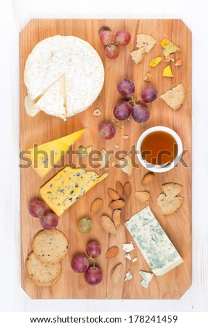 assorted soft cheeses, grapes, nuts and honey on a wooden cutting board, top view, vertical - stock photo