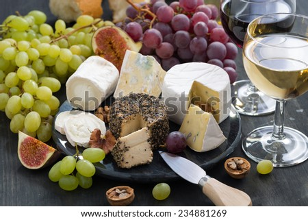 Assorted soft delicacy cheeses and snacks for wine on a dark background, close-up - stock photo