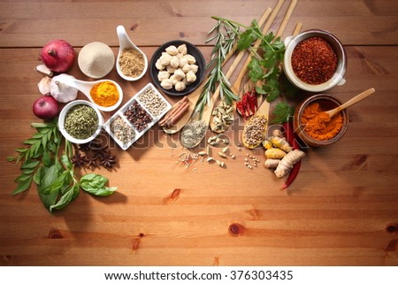 assorted spices and herb on the wooden table - stock photo
