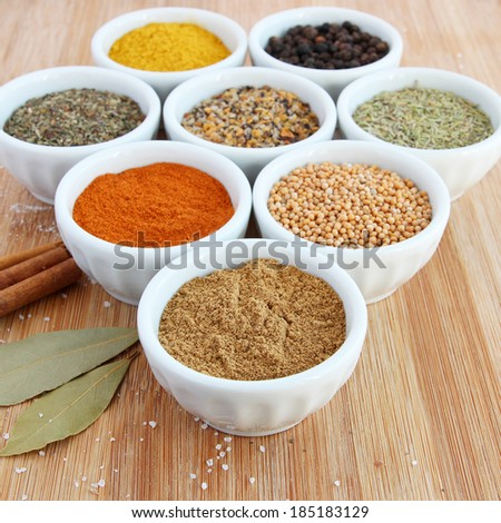 Assorted spices in white bowls - cumin in the foreground