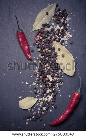 Assorted spices on a black stone background, sea salt, black pepper, red chilli - stock photo