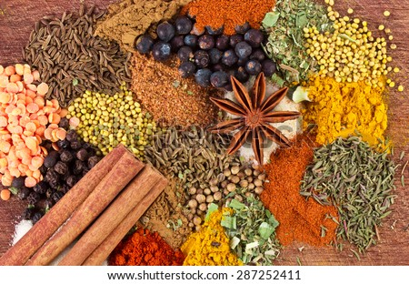 Assorted spices on a wooden board - stock photo