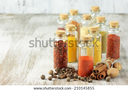 Assorted spices on rustic wood. - stock photo