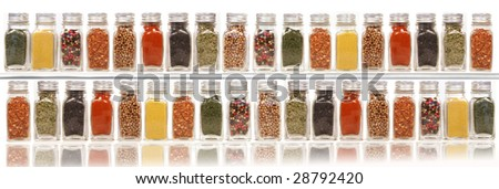 Assorted spices on two layer shelves against white background - stock photo