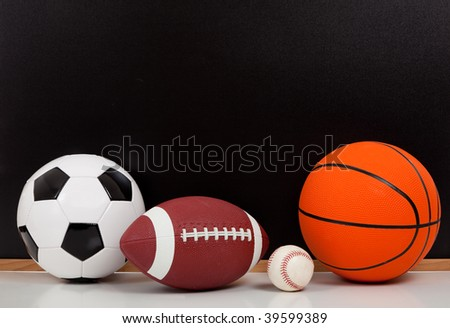 Assorted sports balls including a basketball, american football, soccer ball and baseball on a black chalkboard background - stock photo