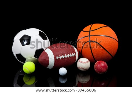 Assorted sports balls including a basketball, american football, soccer ball, tennis ball, baseball, golf ball and cricket ball on a black background - stock photo
