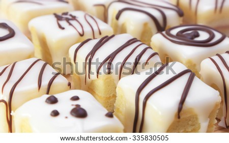 Assorted squares of lemon cake covered in icing and decorated with chocolate. - stock photo