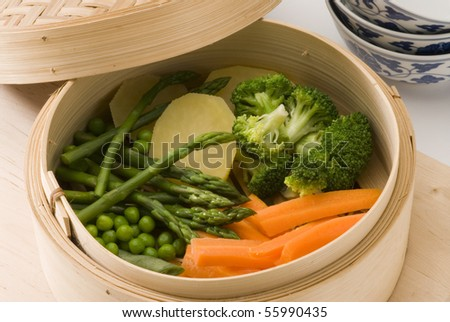 Assorted steamed vegetables in a bamboo steamer. Selective focus. - stock photo
