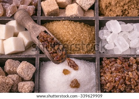 Assorted sugar and wooden scoop closeup.Toned - stock photo