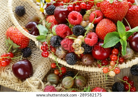 Assorted summer berries (raspberries, strawberries, cherries, currants, gooseberries) - stock photo
