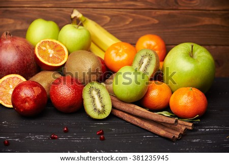 assorted tangerine kiwi apple bananna  orange and pomegranate on rustic wooden table with cinnamon sticks. Shallow depth of field - stock photo