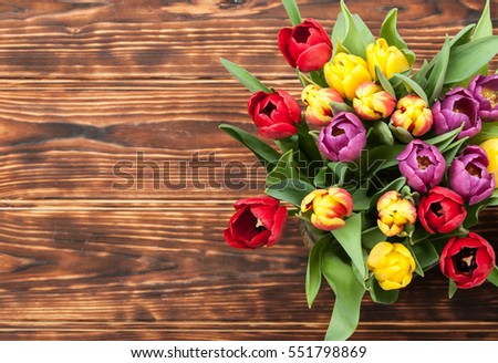 Assorted Tulips Bouquet. Top View. Burned Wooden Background. Copy Space.