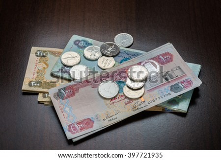 Assorted UAE Dirham currency notes and coins on dark background. - stock photo