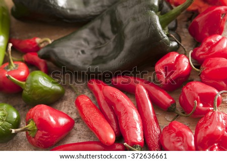 Assorted varieties of fresh whole chili peppers with red hot cayenne, green and black arranged in a full frame overhead background view - stock photo