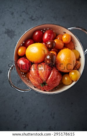 Assorted varieties of tomato in a colander - stock photo