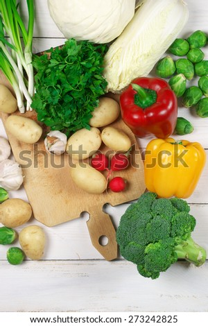 Assorted vegetables and cutting board on white wooden background. Top view point. - stock photo