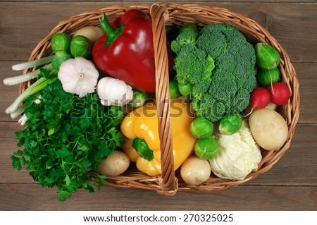 Assorted vegetables in basket on rustic wooden background. Top view point. - stock photo