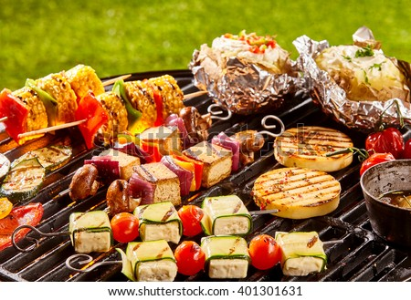 Assorted vegetarian meat alternative patties, vegetables, tofu and potatoes next to olive oil on cookout grill - stock photo