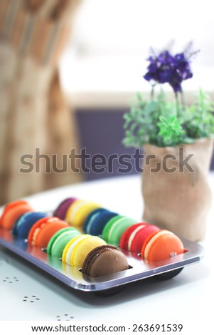 Assorted vivid and tasty macaroons in box on a table in cafe. Nice creamy bokeh and shallow depth of field. - stock photo