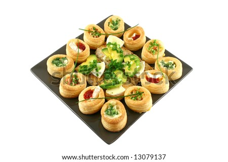 Assorted vol au vonts and avocado and camembert bites on a platter. - stock photo