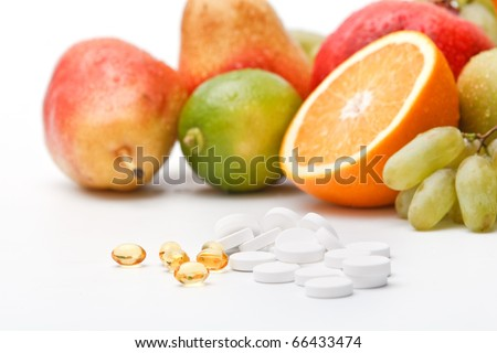 Assorted wet fresh fruits and pills on white background - stock photo