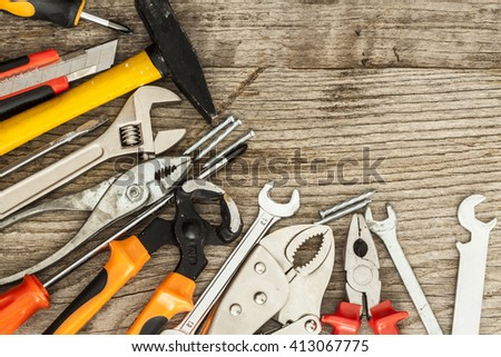 Assorted work tools on wood background - stock photo