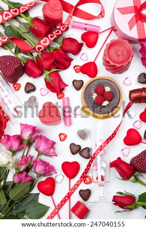 Assortiment of different Valentine Day gifts, candies, red roses, cosmetics, candles, and bottle of Champagne.  - stock photo