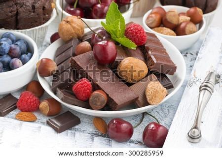 assortment chocolate, berries and nuts, closeup, horizontal - stock photo