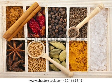 Assortment collection of powder spices on spoons in wooden box background - stock photo